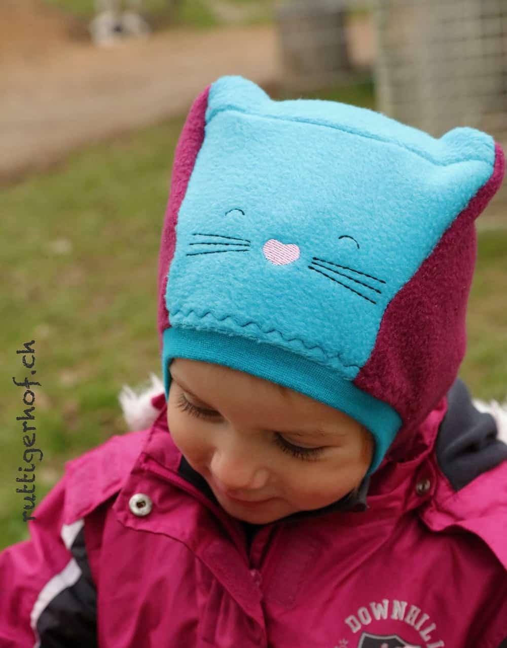 Katzenohrenmütze: Schalmütze mit Katzenohren und aufgesticktem Gesicht. Schalmütze selber nähen
